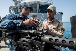 Gunner's Mate 2nd Class Gabriel Lewis discusses an m240 light machine gun's operating procedures and techniques with an Iraqi sailor aboard the Iraqi Offshore Support Vessel Al Basra (OSV 401) during a trilateral exercise between the U.S., Kuwait and Iraqi armed forces in the Arabian Gulf, March 15, 2017. (U.S. Navy Combat Camera photo by Mass Communication 2nd Class Corbin J. Shea)
