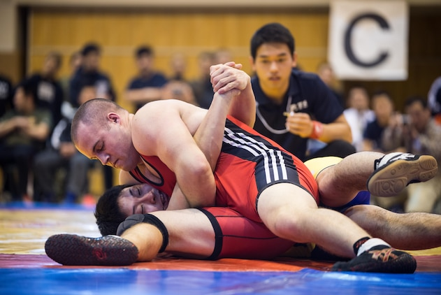 "Pfc. Scott Lohndorf, assigned to Headquarters and Headquarters Squadron from Marine Corps Air Station Iwakuni, wrestles his opponent during the 23rd Annual All Japan Self-Defense Force Wrestling Tournament in Camp Asaka, Japan. Lohndorf wrestled with the ""Seahawks"" Navy Wrestling Team from Fleet Activities Yokosuka. (Courtesy photo by Mass Communication Specialist 1st Class Anthony R. Martinez)"