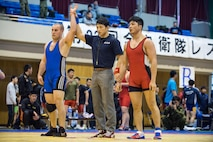"Pfc. Scott Lohndorf, assigned to Headquarters and Headquarters Squadron from Marine Corps Air Station Iwakuni, wins his match during the 23rd Annual All Japan Self-Defense Force Wrestling Tournament in Camp Asaka, Japan. Lohndorf wrestled with the ""Seahawks"" Navy Wrestling Team from Fleet Activities Yokosuka. (Courtesy photo by Mass Communication Specialist 1st Class Anthony R. Martinez)"