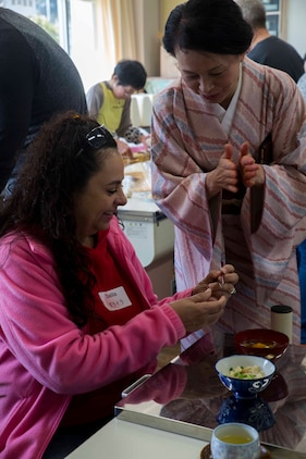 Dalila Garavito, a Marine Corps Air Station Iwakuni resident, learns how to use hashi (chop sticks) during the cultural exchange at Tsuzu Elementary School at Iwakuni City, Japan, March 11, 2017. During the event, a traditional tea ceremony was demonstrated and a cooking class was held to teach people how to make common Japanese dishes. The event taught residents from MCAS Iwakuni about Japanese culture, which brought Americans and Japanese together. (U.S. Marine Corps photo by Lance Cpl. Gabriela Garcia-Herrera)