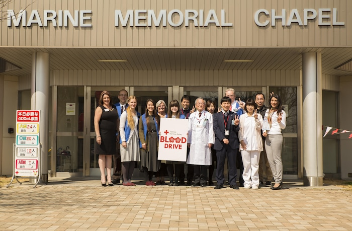 The Marine Corps Air Station Iwakuni Red Cross Society and Japanese Red Cross Society volunteers pose in front of the Marine Memorial Chapel during a blood drive at MCAS Iwakuni, Japan, March 7, 2017. The volunteers collaborated together and collected approximately 24,000 milliliters of blood from 59 Japanese and American donors. (U.S. Marine Corps photo by Pfc. Stephen Campbell)