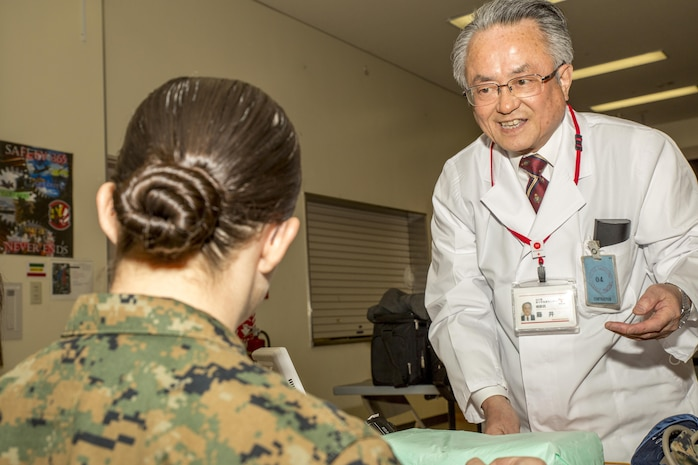 Dr. Terumasa Fujii, with the Japanese Red Cross Society, greets a U.S. Marine during the blood drive at Marine Corps Air Station Iwakuni, Japan, March 7, 2017. Dr. Fujii was responsible for checking the donor's blood pressure before giving blood. The drive ended with a total of 59 donors, 15 of which were U.S. service members, and approximately 24,000 milliliters of blood.  (U.S. Marine Corps photo by Pfc. Stephen Campbell)