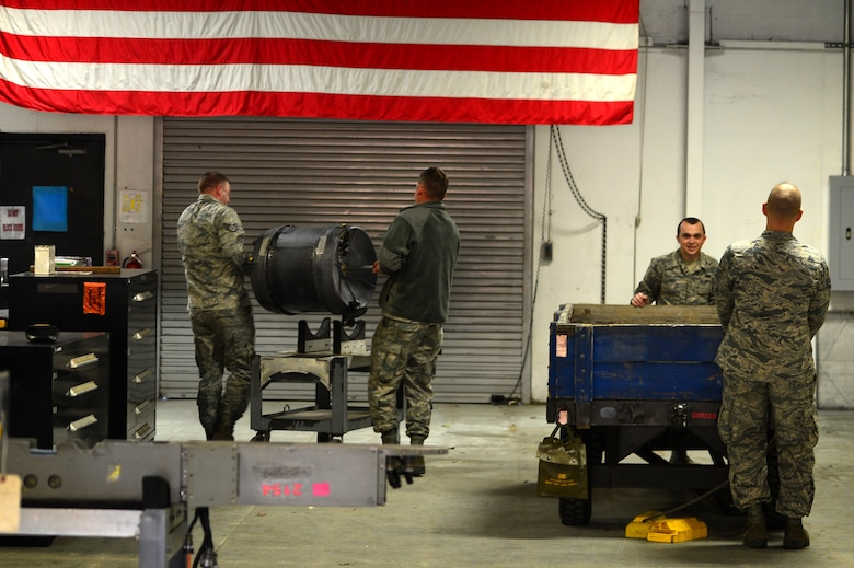 U.S. Airmen assigned to the 20th Equipment Maintenance Squadron aircraft armament flight load parts of an M-61A1 20 mm multi-barrel cannon onto an inspection platform at Shaw Air Force Base, S.C., March 29, 2017. The cannon being inspected is comprised of six barrels and is tested for operations security before being installed onto an F-16CM Fighting Falcon. (U.S. Air Force photo by Airman 1st Class Christopher Maldonado)