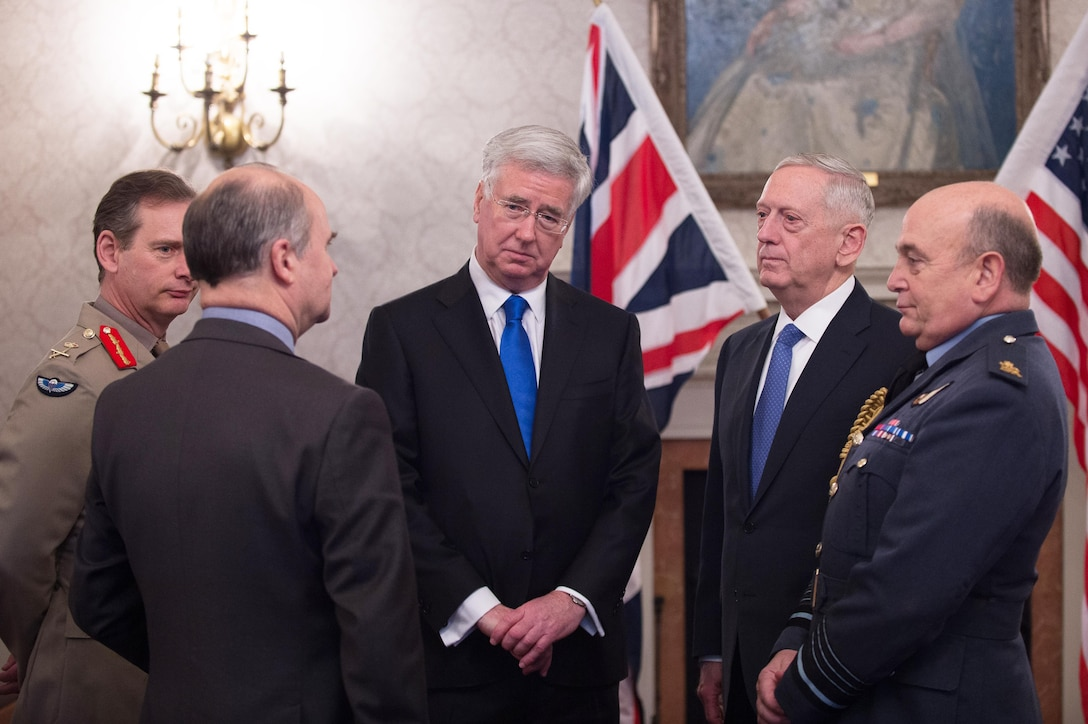 Defense Secretary Jim Mattis speaks with British Defense Secretary Michael Fallon, center, before an arrival ceremony at Britain's Defense Ministry in London.