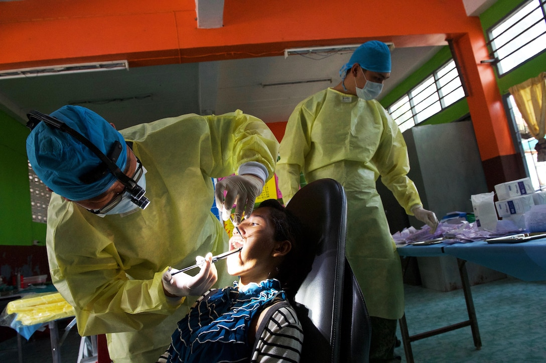 Republic of Singapore Air Force dentists provide treatment for a Thai local during an exercise Cope Tiger 17 (CT17) combined civic action engagement at a school in Nakhon Ratchasima Province, Thailand, March 22, 2017. The combined civic action engagement provided an outlet for the countries participating in CT17 to give back to the community surrounding Korat Royal Thai Air Force Base. Over 1,200 U.S., Thai and Singaporean military members participated in this year's annual multilateral exercise. (U.S. Air Force photo/Staff Sgt. Kamaile Chan)