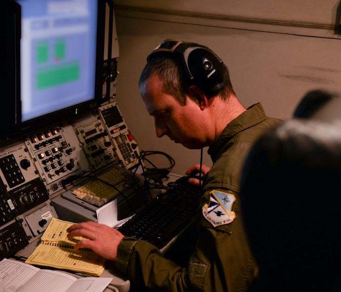 A member of the 963rd Airborne Air Control Squadron works diligently during a training mission, March, 15, 2017, while flying over the Pacific Northwest. The AWACS is an airborne air control squadron capable of providing early warning coverage for the area of responsibility being controlled. (U.S. Air Force photo by Senior Airman Jessica H. Smith/RELEASED)