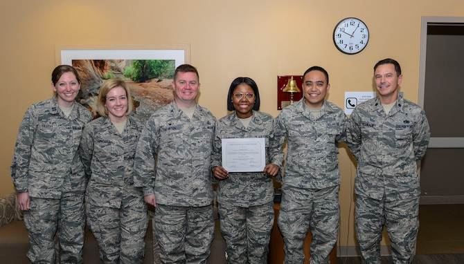 1st Lt. Tyesha McBride, 99th Mission Support Group executive officer, is presented with a certificate of achievement for completing her cancer treatment on March 21, 2017, in the Mike O'Callaghan Medical Center at Nellis Air Force Base, Nev. McBride was diagnosed with Hodgkin's lymphoma which is a cancer of the lymphatic system. (U.S. Air Force photo by Airman 1st Class Nathan Byrnes)