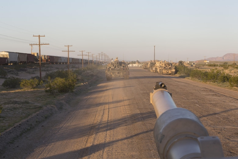 1st Tank Battalion waits for a train to pass while traveling from Ft. Irwin, Calif., to Marine Corps Air Ground Combat Center, Twentynine Palms, Calif., during Exercise Desert March, March 27, 2017. He exercise was made to test the battalion's capabilities in handling a long distance movement as well as test the battalion's capabilities of logistically supporting the battalion throughout the exercise.  (U.S. Marine Corps photo by Cpl. Thomas Mudd)