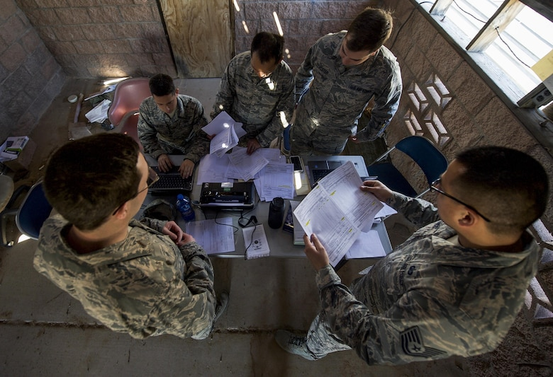 A team of U.S. Air Force contracting officers review offers after meeting with simulated vendors during a training exercise organized by the 99th Contracting Squadron on Nellis Air Force Base, Nev., March 16, 2017. The exercise was spread over two days, one day for lectures and scenarios followed by one day in the field with the challenges of a bare base environment. (U.S. Air Force photo by Airman 1st Class Kevin Tanenbaum/Released)