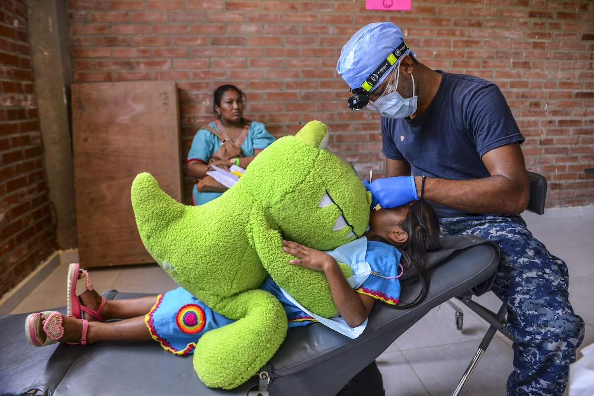 A sailor cleans a child's teeth as she holds a large stuffed animal.