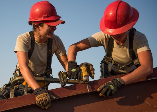Senior Airman Paige Rodgers and Staff Sgt. Keny Drescher-Brown, 823rd Red Horse Squadron, share a moment of levity while they position and drill a beam into place March 23 during a construction project at Eglin Air Force Base, Fla. The 96th Civil Engineer Group's open air pavilion is one of many troop training projects the 823rd RHS will complete for the Department of Defense, the Air Force and the local community to maintain their skills until the next deployment. (U.S. Air Force photo/Ilka Cole)