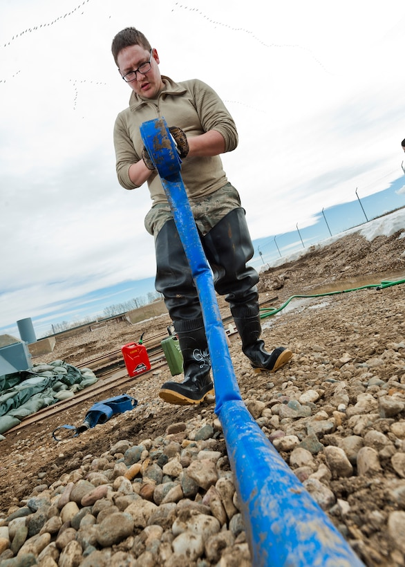 Senior Airman Matthew Singer, 91st Missile Maintenance Squadron electromechanical team technician, winds up a hose near Bowbells, N.D., March 29, 2017. The electromechanical team technicians measured rising water levels and relocated water, snow and mud away from critical 91st MW assets. (U.S Air Force photo/Senior Airman J.T. Armstrong)