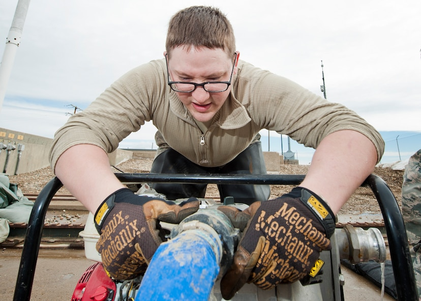 Senior Airman Matthew Singer, 91st Missile Maintenance Squadron electromechanical team technician, removes a hose from a water-pump near Bowbells, N.D., March 29, 2017. The electromechanical team technicians measured rising water levels and relocated water, snow and mud away from critical 91st MW assets. (U.S Air Force photo/Senior Airman J.T. Armstrong)