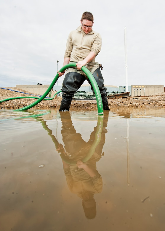 Senior Airman Matthew Singer, 91st Missile Maintenance Squadron electromechanical team technician, finishes draining flood-water from a launch facility near Bowbells, N.D., March 29, 2017. Singer used a water-pump and hose to drain and relocate water to a safe level. (U.S Air Force photo/Senior Airman J.T. Armstrong)