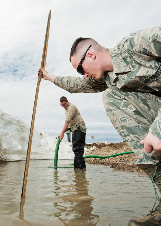 (From right) Airman 1st Class Heath Rauch and Senior Airman Matthew Singer, 91st Missile Maintenance Squadron electromechanical team technicians, measures and remove flood-water near Bowbells, N.D., March 29, 2017. Rauch and Singer worked with to drain water to a safe level. (U.S Air Force photo/Senior Airman J.T. Armstrong)