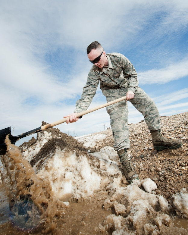 Airman 1st Class Heath Rauch, 91st Missile Maintenance Squadron electromechanical team technician, shovels snow and mud at a launch facility near Bowbells, N.D., March 29, 2017. Rauch was a part of a two-man team responsible for relocating flood-water away from critical assets at the launch facility. (U.S Air Force photo/Senior Airman J.T. Armstrong)