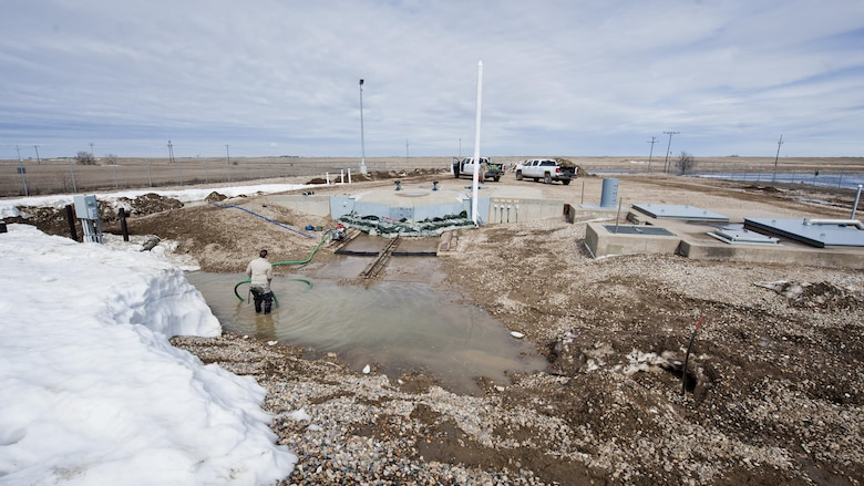 Airmen from the 91st Missile Maintenance Squadron drain flood-water from a launch facility near Bowbells, N.D., March 29, 2017. The electromechanical team technicians measured rising water levels and relocated water, snow and mud away from critical 91st MW assets. (U.S Air Force photo/Senior Airman J.T. Armstrong)