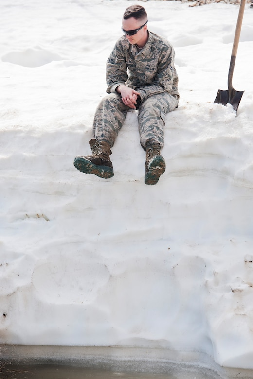 Airman 1st Class Heath Rauch, 91st Missile Maintenance Squadron electromechanical team technician, sits atop a snowbank above flood-water at a launch facility near Bowbells, N.D., March 29, 2017. Rauch was a part of a two-man team responsible for relocating flood-water away from critical assets at the launch facility. (U.S Air Force photo/Senior Airman J.T. Armstrong)