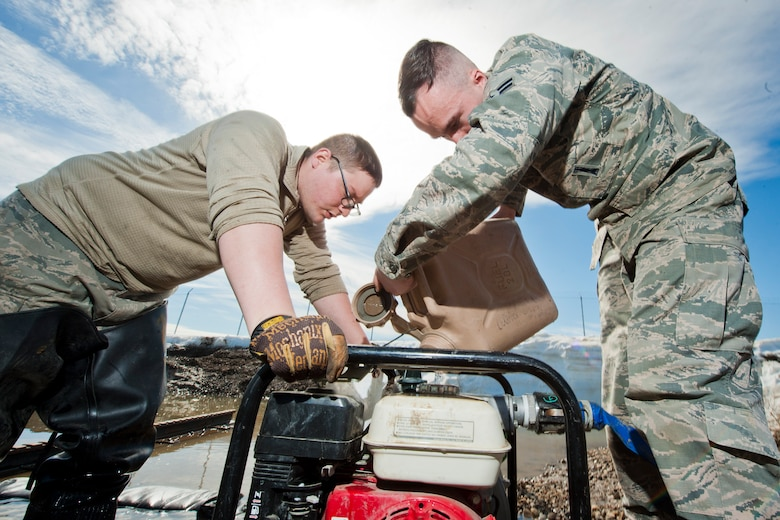 Airman 1st Class Heath Rauch, 91st Missile Maintenance Squadron electromechanical team technician, pours water into a pump near Bowbells, N.D., March 29, 2017. The two-man team used a water-pump to relocate flood-water away from critical assets at the launch facility. (U.S Air Force photo/Senior Airman J.T. Armstrong)