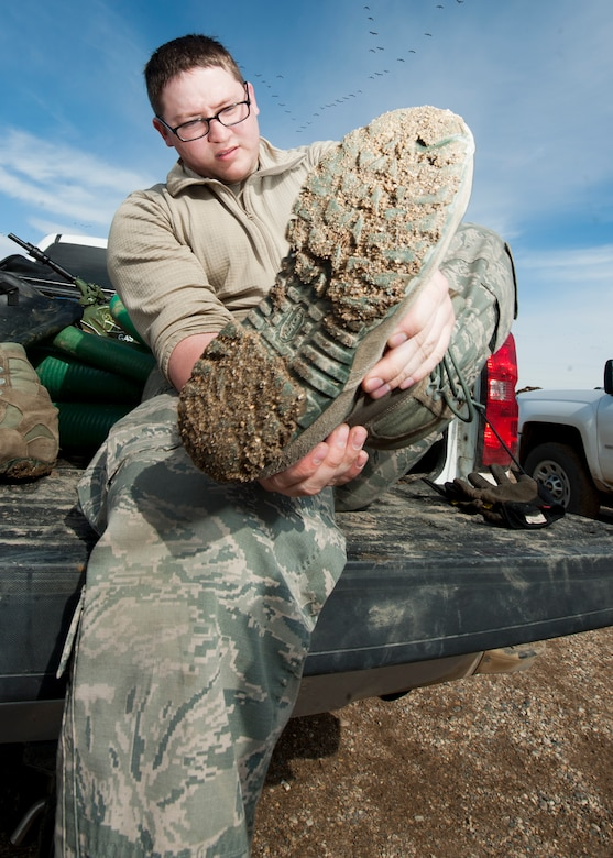 Senior Airman Matthew Singer, 91st Missile Maintenance Squadron electromechanical team technician, removes his boot at a launch facility near Bowbells, N.D., March 29, 2017. Singer was a part of a two-man team responsible for relocating flood-water away from critical assets at the launch facility. (U.S Air Force photo/Senior Airman J.T. Armstrong)