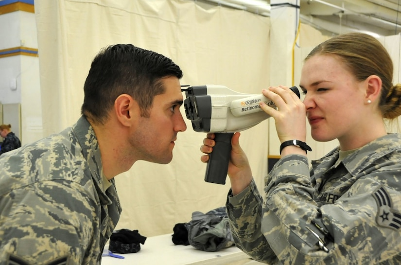 Air Force Senior Airman Lauren Scheonore with the 147th Medical Group Texas Air National Guard and Air Force Staff Sgt. Keith Wuetig with the 434th Aerospace Medical Squadron train on how to properly use a retinal scanner before seeing patients during Arctic Care 2017 in Kodiak, Alaska, March 27, 2017. Arctic Care 2017 is a civil-military collaboration intended to build on mutually beneficial partnerships between U.S. communities and the Defense Department. It provides training opportunities for U.S. military and Canadian Health service members to prepare for worldwide deployment while supporting the needs of underserved communities on Kodiak Island, Alaska. Air Force photo by Master Sgt. Luke Johnson