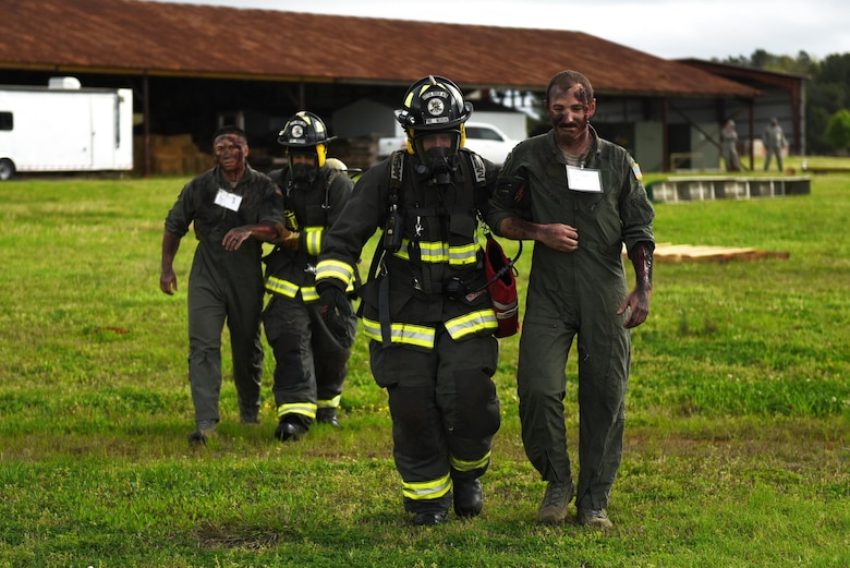 U.S. Air Force Senior Airman Lance Hendricks and U.S. Air Force Michael Leger, 19th Civil Engineer Squadron Fire Department firefighters, escort simulated crash victims to safety during a major accident response inspection March 30, 2017, at the Jacksonville Fire Department Training Center, Ark. Aircraft parts and simulated flare shells were arranged to replicate debris. (U.S. Air Force photo by Airman 1st Class Kevin Sommer Giron)