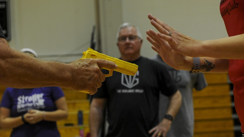 """Michael """"Moose"""" Moore, founder of The Vigilance Group, demonstrates defensive techniques used to get away from a perpetrator with a handgun to a group of Air Commando spouses at Hurlburt Field, Fla., March 31, 2017. This training provides techniques to avoid danger and actions to take if violence is not preventable. (U.S. Air Force photo by Airman 1st Class Isaac O. Guest IV)"""