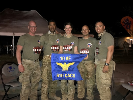 (Left to Right) U.S. Air Force Reservists, Master Sgt. John Herrick, 39, who has completed three other marathons; Staff Sgt. Tyrone Hawkins, 47, an avid cyclist; 2nd Lt. Amber Schoenberger, a direct descendent of a Bataan Death March survivor; Tech. Sgt. Delbert Templeton, 36, a prior Marine; and Tech. Sgt. Trevor Petersma, 39, who completed the Air Force half marathon while deployed in Iraq in 2008, all members of the 610th Command and Control Squadron, pose behind their unit guidon after completing the Bataan Memorial Death March Marathon March 19 at White Sands Missile Range, NM. (Courtesy photo)
