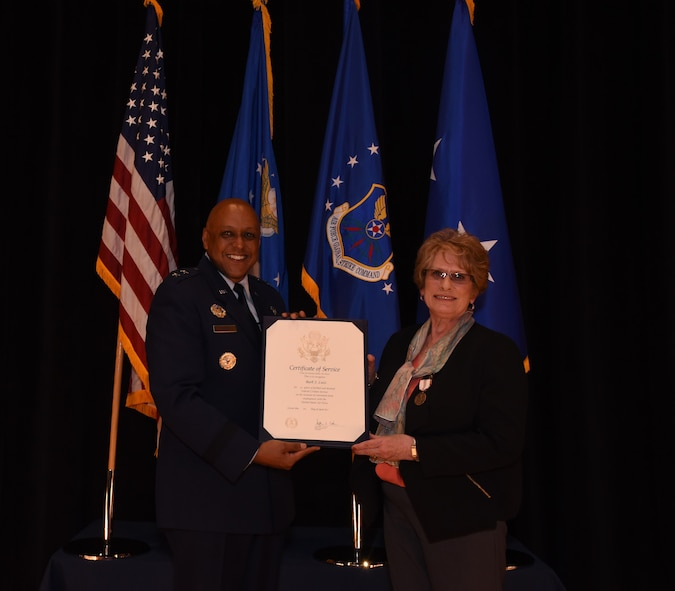 Maj. Gen. Anthony Cotton, 20th Air Force and Task Force 214 commander,  presents Barbara Lutz, 20th Air Force executive assistant to the commander, with her retirement certificate at F.E. Warren Air Force Base, Wyo.,  Mar. 31, 2017.  Lutz is retiring after 43 years of distinguished federal civil service.
