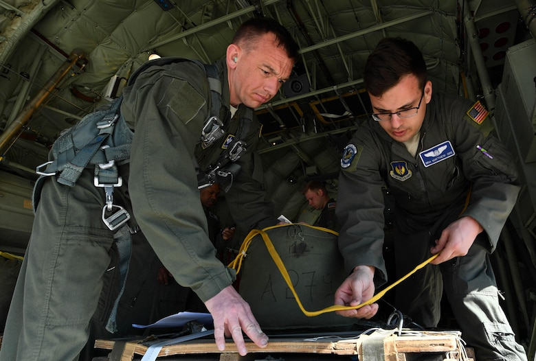 U.S. Air Force Senior Airman Matthew Gee, 37th Airlift Squadron loadmaster, prepares a low-cost low-altitude cargo for an air drop while Master Sgt. CJ Campbell, 37th AS aircraft loadmaster, supervises during Exercise Stolen Cerberus IV at Elefsis Air Base, Greece, April 19, 2017. Gee, Campbell, and another loadmaster worked with the Hellenic air force to set up four LCLA cargos for a drop. Combined exercises such as these enhance the interoperability capabilities and skills among allied and partner armed forces. (U.S Air Force photo by Senior Airman Tryphena Mayhugh)