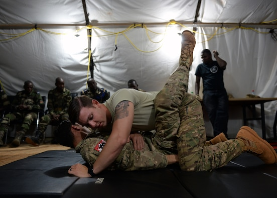 Senior Airmen Joshua Brooks and Jacob Myers, 768th Expeditionary Air Base Squadron air advisors, demonstrate a jiu jitsu maneuver to members of the Forces Armées Nigeriennes at Nigerien Air Base 101, Niger, April 4, 2017. The training was part of a larger joint knowledge exchange to help train and build relations with the FAN. (U.S. Air Force photo by Senior Airman Jimmie D. Pike)