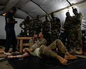 Members of the Forces Armées Nigeriennes watch as Senior Airman Joshua Brooks, 768th Expeditionary Air Base Squadron air advisor, demonstrates an armbar at Nigerien Air Base 101, Niger, April 4, 2017. The training was part of a larger joint knowledge exchange to help train and build relations with the FAN. (U.S. Air Force photo by Senior Airman Jimmie D. Pike)