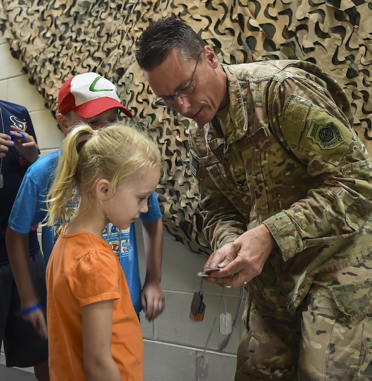 Col. Tom Palenske, the commander of the 1st Special Operations Wing, helps military children find their dog tags during Operation Kids Understanding Deployment Operations at Hurlburt Field, Fla., April 22, 2017. Children processed through a deployment line where they received dog tags, shirts and deployment bags. (U.S. Air Force photo by Airman 1st Class Joseph Pick)