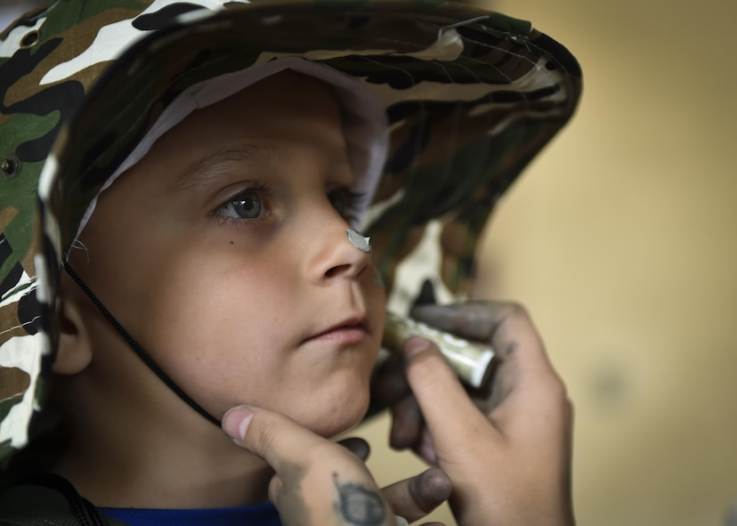 A military child gets his face painted prior to deploying during Operation Kids Understanding Deployment Operations at Hurlburt Field, Fla., April 22, 2017. Operation KUDOS is an educational event aimed to help build resilience in military youth by engaging them in activities that simulate the pre-deployment experience, such as pre-deployment lines and demonstrations. (U.S. Air Force photo by Airman 1st Class Joseph Pick)