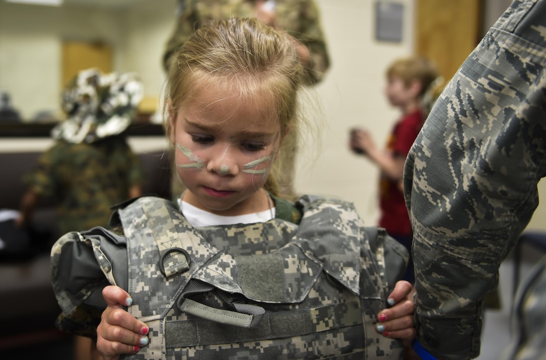 A military child puts on a vest before deploying during Operation Kids Understanding Deployment Operations at Hurlburt Field, Fla., April 22, 2017. Operation KUDOS is an educational event aimed to help build resilience in military youth by engaging them in activities that simulate the pre-deployment experience, such as pre-deployment lines and demonstrations. (U.S. Air Force photo by Airman 1st Class Joseph Pick)