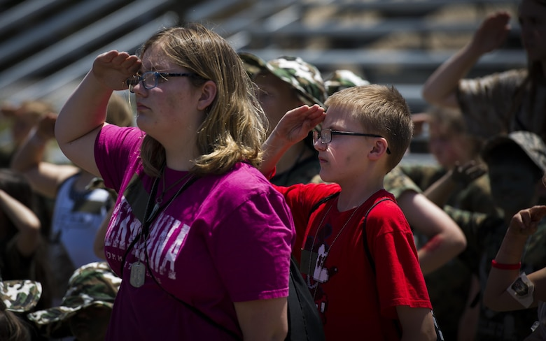 Military children render salutes through the playing of retreat during Operation Kids Understanding Deployment Operations at Hurlburt Field, Fla., April 22, 2017. Operation KUDOS concluded with a homecoming where parents welcomed back their children. (U.S. Air Force photo by Airman 1st Class Joseph Pick)