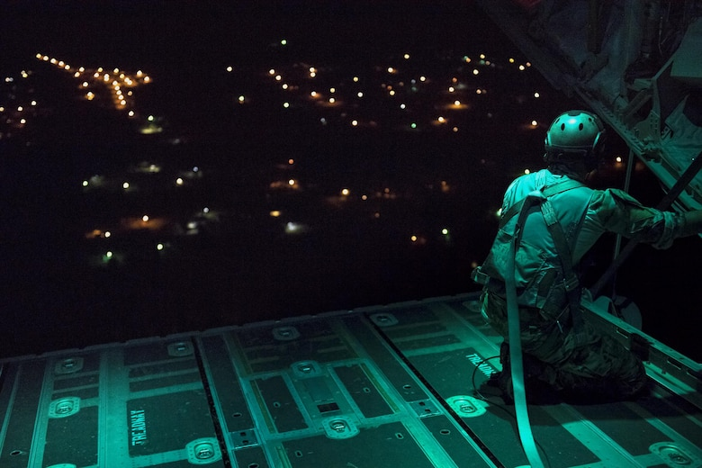 A pararescueman from the 38th Rescue Squadron scans the drop zone from the back of an HC-130J Combat King II prior to static-line jumps, April 24, 2017, at Moody Air Force Base, Ga. All PJs are qualified to conduct both static-line and High altitude, low opening jumps. During a static-line jump, the jumper is attached to the aircraft via the 'static-line', which automatically deploys the jumpers' parachute after they've exited the aircraft. (U.S. Air Force photo by Staff Sgt. Ryan Callaghan)