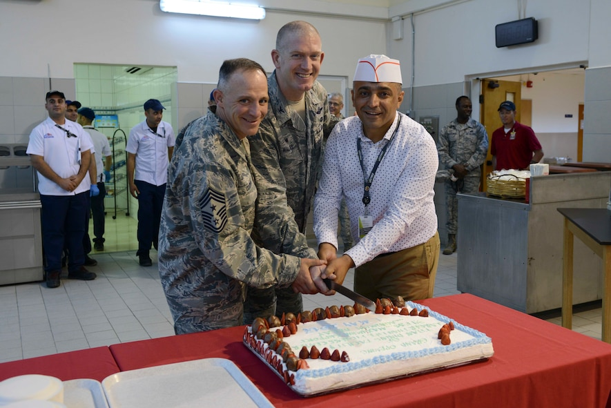 U.S. Air Force Command Chief Master Sgt. Thomas Cooper (left), Col. John Walker, 39th Air Base Wing commander (center), and Mehmet Kahvecioglu, senior Turkish manager for food services, cut a cake at the grand opening of the Larger Than Life Fitness Center and Titan Dining Facility May 1, 2017, at Incirlik Air Base, Turkey. Both facilities were opened in the former Department of Defense Dependents School on base. (U.S. Air Force photo by Airman 1st Class Devin M. Rumbaugh)