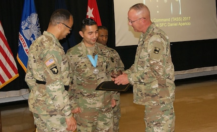 Sgt. 1st Class Daniel Aparicio (center) receives the Sgt. Audie Murphy Club Medal, Army Commendation Medal, and a bronze eagle from Maj. Gen. A.C. Roper (left), commander of the 80th Training Command, and Command Sgt. Maj. Jeffrey Darlington (right), the senior enlisted leader of the 80th TC, at the SAMC Induction Ceremony at Fort Devens, Massachusetts, April 6, 2017.