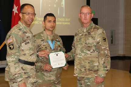 Sgt. 1st Class Daniel Aparicio (center) receives the Sgt. Audie Murphy Club Medal and Army Commendation Medal from Maj. Gen. A.C. Roper (left), commander of the 80th Training Command, and Command Sgt. Maj. Jeffrey Darlington (right), the senior enlisted leader of the 80th TC, at the SAMC Induction Ceremony at Fort Devens, Massachusetts, April 6, 2017.