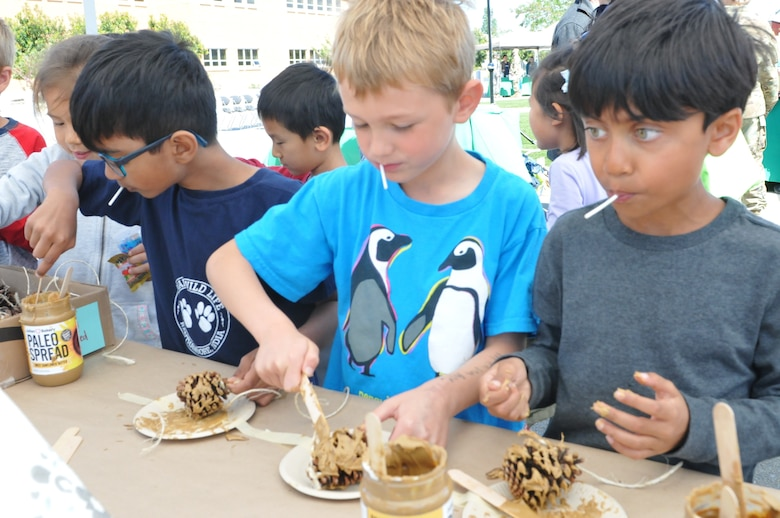Students from a local elementary school creates bird feeders with pine cones, peanut butter and bird seeds at an Earth Day booth facilitated by the 63rd Regional Support Command Department of Public Works Environmental Team.