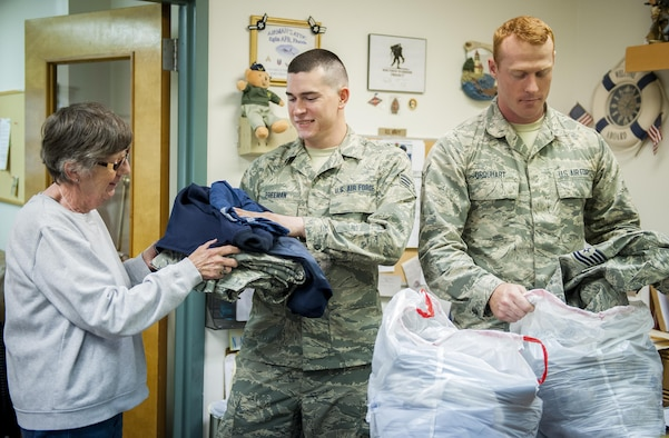 Senior Airman Skylar Freeman (center) and Airman 1st Class Jeffrey Urquhart, from the 96th Logistics Readiness Squadron, hand donated uniform items to Fran Moore, an Airman's Attic volunteer, during Volunteer Week, observed April 24 -28 at Eglin Air Force Base, Fla.  The Airmen volunteered a few hours at the Airman's Attic for service members in need.  (U.S. Air Force photo/Kevin Gaddie)