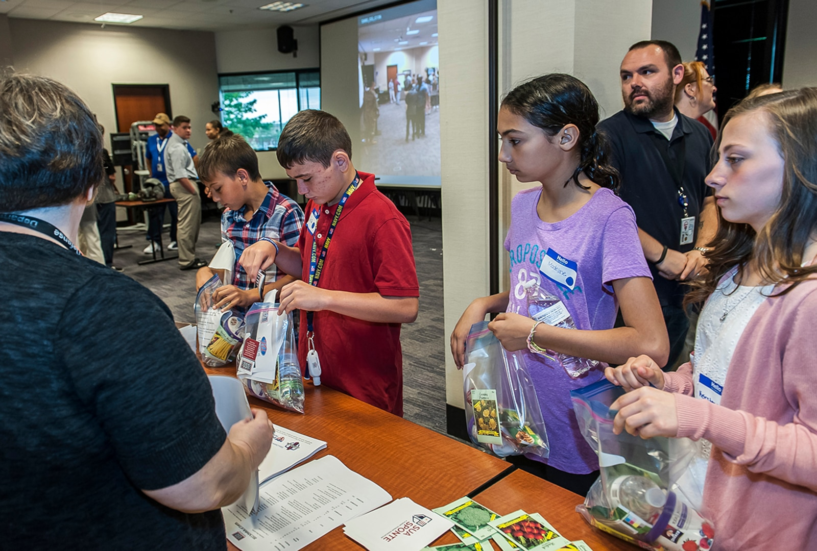 """Children line up to create USO care packages for disabled and homeless veterans during DSCC's 'Take our daughters and sons to work day'. More than 100 children of DLA Land and Maritime and DFAS Columbus associates attended the annual event. This year's them was """"Count on Me."""""""