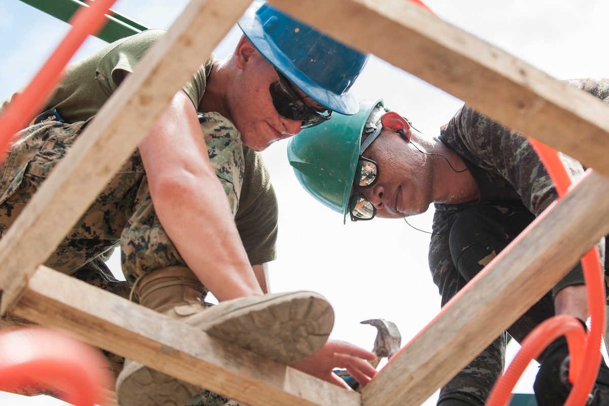 A U.S. Marine and Philippine soldier install electrical wire casing in a new classroom.