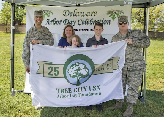 Col. Randy Boswell, 436th Mission Support Group commander, holds the Tree City USA flag with Master Sgt. Donald Bourne, 736th Aircraft Maintenance Squadron airframe power plant general section chief, and his family April 28, 2017, at Dover Air Force Base, Del. Bourne's daughter, Audriana, won the Kindergarten-level for Kent County in an Arbor Day poster contest. (U.S. Air Force photo by Senior Airman Zachary Cacicia)
