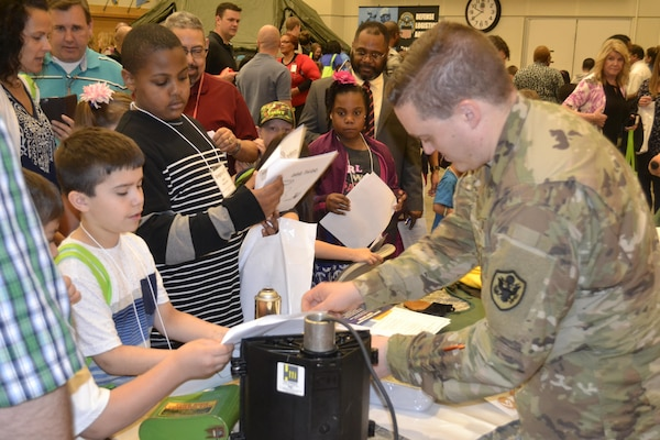 Army Lt. Col. Paul McCullough, Construction and Equipment supply chain program manager for audit readiness, places stickers on children's scavenger hunt worksheets in the DLA Troop Support Bldg. 6 auditorium as part of Take Our Daughters and Sons to Work Day April 27, 2017. More than 440 children participated in interactive activities to learn more about the missions of DLA Troop Support and NAVSUP Weapon Systems Support.