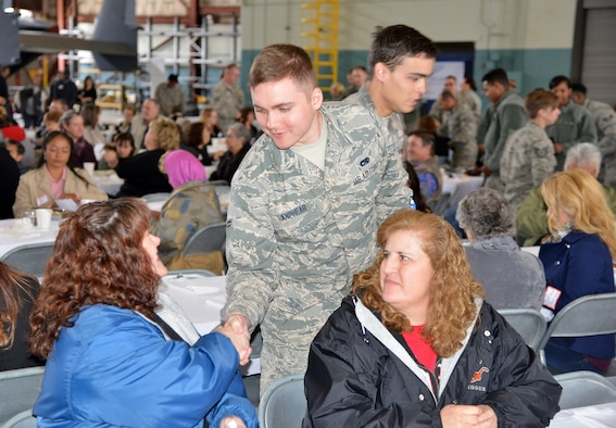 Airman 1st Class Shawn Lanphear, 58th Maintenance Group, presents a commerorative coin to guest Sheryl McGartland as Aurora Garcia looks on. The coining concluded the Warriors to Warriors event, conducted to raise awareness and encourage people in the fight against Ovarian Cancer April 29 at Hanagar 1000.