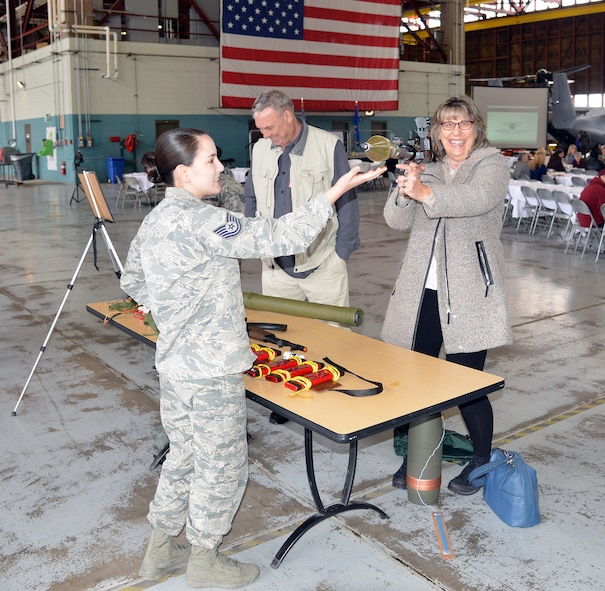 Marsha Demento (right) gets familiar with a mock RPG as Tech. Sgt. Vironica Reams, 58th Operations Support Squadron, assists. Marsha's brother Ed (center) is also looking at training aides on display during the April 25 Warriors to Warriors event at Hangar 1000. The event was conducted to raise awareness and encourage people in the fight against Ovarian Cancer.
