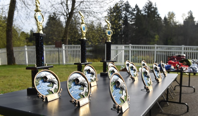 Trophies are lined up to be presented to winners during the Annual McChord Field Top III Children's Fishing Derby April 29, 2017 at Carter Lake on McChord Field, Wash. More than 100 people came out to participate in this year's fishing derby. (U.S. Air Force Photo/ Staff Sgt. Naomi Shipley)