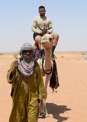 Staff Sgt. Lorrentis Oliver, Staff Sgt. Lorrentis Oliver, 31st Expeditionary Rapid Engineer Deployable Heavy Operational Repair Squadron Engineers heavy equipment operator, rides a camel during a bazaar at Nigerien Air Base Squadron 201, Niger, April 16, 2017. Profits made from the bazaar went go to help feed families and stimulate the economy in the local community. (U.S. Air Force photo by Senior Airman Jimmie D. Pike)